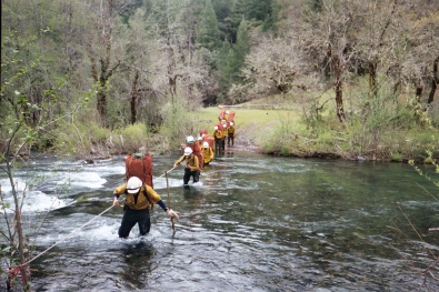 Rookie smokejumper candidates cross a creek during a packout training excersize | Redding, CA | GACC